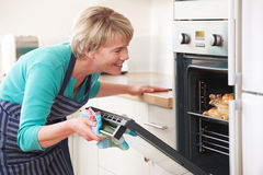 Woman Looking At Chicken Roasting In Oven Stock Photo