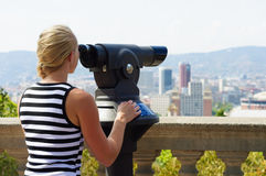 Woman looking through city viewer Stock Image