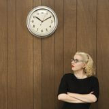 Woman looking at clock. Royalty Free Stock Image