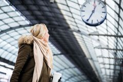 Woman looking at clock in train station as her train has a delay. Woman looking impassionate at clock in train station as her train has a delay Royalty Free Stock Image