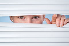 Woman Looking Through Closed Blinds Royalty Free Stock Image