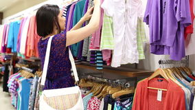 Woman looking through clothes stock video