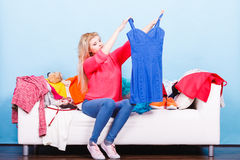 Woman looking through clothes on messy couch Stock Images