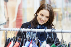 Woman Looking At Clothes On Rail In Shopping Mall Royalty Free Stock Photos