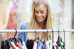 Woman Looking At Clothes On Rail In Shopping Mall Stock Photos