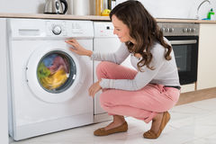 Woman Looking At Clothes Rotating Inside The Washing Machine Royalty Free Stock Photography