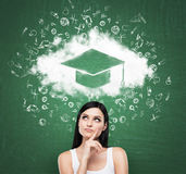 Woman looking at the cloud with graduation hat over the head. Green chalk board as a background. Stock Images