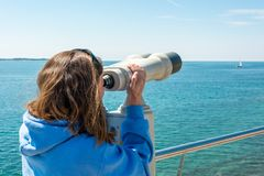 Woman looking through coin operated binoculars at seaside. Royalty Free Stock Photos