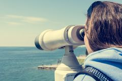 Woman looking through coin operated binoculars at seaside. Stock Photography