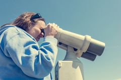 Woman looking through coin operated binoculars at seaside. Royalty Free Stock Photography
