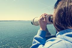 Woman looking through coin operated binoculars at seaside. Stock Photos