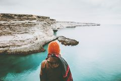 Woman looking at cold sea view alone Travel Lifestyle. Concept adventure vacations outdoor. Girl wearing fashion orange knitted hat and scarf. Melancholy Stock Photography
