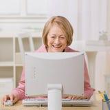 Woman looking at computer monito. Laughing senior woman sitting at desk looking at computer monitor Stock Photography