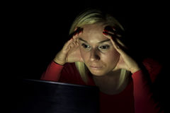 Woman looking at a computer screen in the dark Royalty Free Stock Photography
