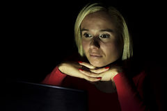 Woman looking at a computer screen at night Royalty Free Stock Photography