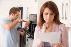Woman Looking Concerned At Bill For Repair Of Kitchen Appliance Royalty Free Stock Photo