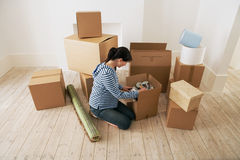 Woman Looking At Contents Of Moving Boxes. Young woman looking at contents of moving boxes in new home Royalty Free Stock Images