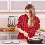 Woman looking a cookbook while standing in her kitchen Royalty Free Stock Images