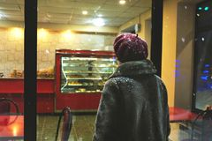 Woman looking at the cosy bakery window full of different cookies on a winter night Stock Photo