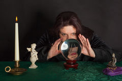 A woman is looking into a crystal ball Stock Photography