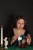 A woman is looking into a crystal ball Stock Image