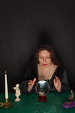 A woman is looking into a crystal ball Royalty Free Stock Photography