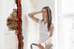 Woman looking at damage after a water pipe leak. At home stock photos