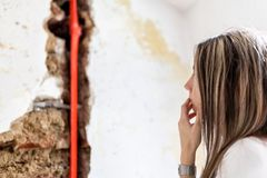 Woman looking at damage after a water pipe leak. At home Royalty Free Stock Photo