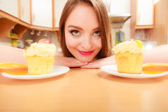 Woman looking at delicious sweet cake. Gluttony. Stock Photos
