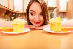 Woman looking at delicious sweet cake. Gluttony. Royalty Free Stock Photo
