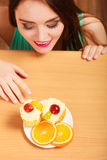 Woman looking at delicious sweet cake. Gluttony. Stock Image