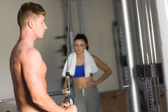 Woman looking at determined man use the lat machine in gym Royalty Free Stock Photos