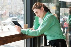 Woman looking at digital tablet with blank screen in coffee shop royalty free stock photo