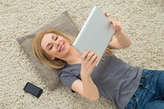 Woman Looking At Digital Tablet While Lying On Carpet Royalty Free Stock Images