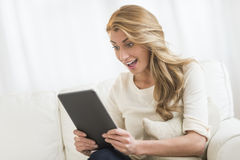 Woman Looking At Digital Tablet While Sitting On Sofa Stock Photos