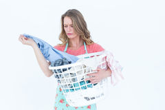 Woman looking at dirty clothes. On white background stock photo
