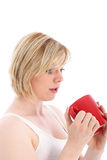 Woman looking with dismay at empty mug. Woman looking with dismay at the bottom of her empty coffee mug isolated on white royalty free stock image