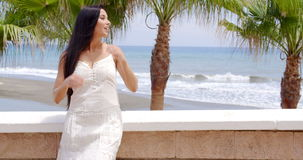 Woman Looking into the Distance on Tropical Beach. Waist Up Portrait of Attractive Woman with Long Dark Hair Looking Wistfully into the Distance with View of stock video footage