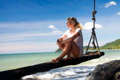 Woman looking into the distance on the tropical beach. On wooden swing stock photos