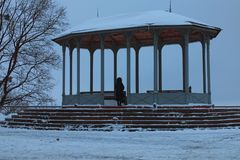 Woman is looking into the distance in vintage pavilion on the Vladimir Hill, it is one of the best parks in Kyiv, Ukraine. Winter morning view Stock Photography
