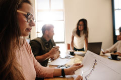 Woman looking at document during meeting in conference room Royalty Free Stock Images