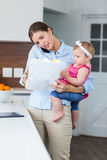 Woman looking in documents while carrying baby girl Royalty Free Stock Photos