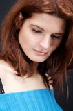 Woman looking down.. Girl,in blue blouse, on black background royalty free stock image