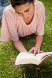 Woman looking down at a book while lying in grass Stock Image
