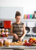 Woman looking down while cutting apples in kitchen Royalty Free Stock Image