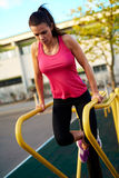 Woman looking down doing tricep dips outside Royalty Free Stock Photography