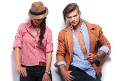 Woman looking down while her boyfriend poses. Casual young women looking down while her boyfriend looks to the camera and poses Stock Images