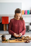 Woman looking down in kitchen preparing garlic and mushrooms Stock Photos