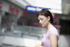 Woman Looking Down In Shopping Centre. Side view of young women looking down in shopping centre stock photo