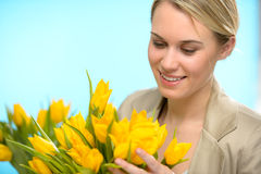 Woman looking down at spring yellow tulips Royalty Free Stock Images
